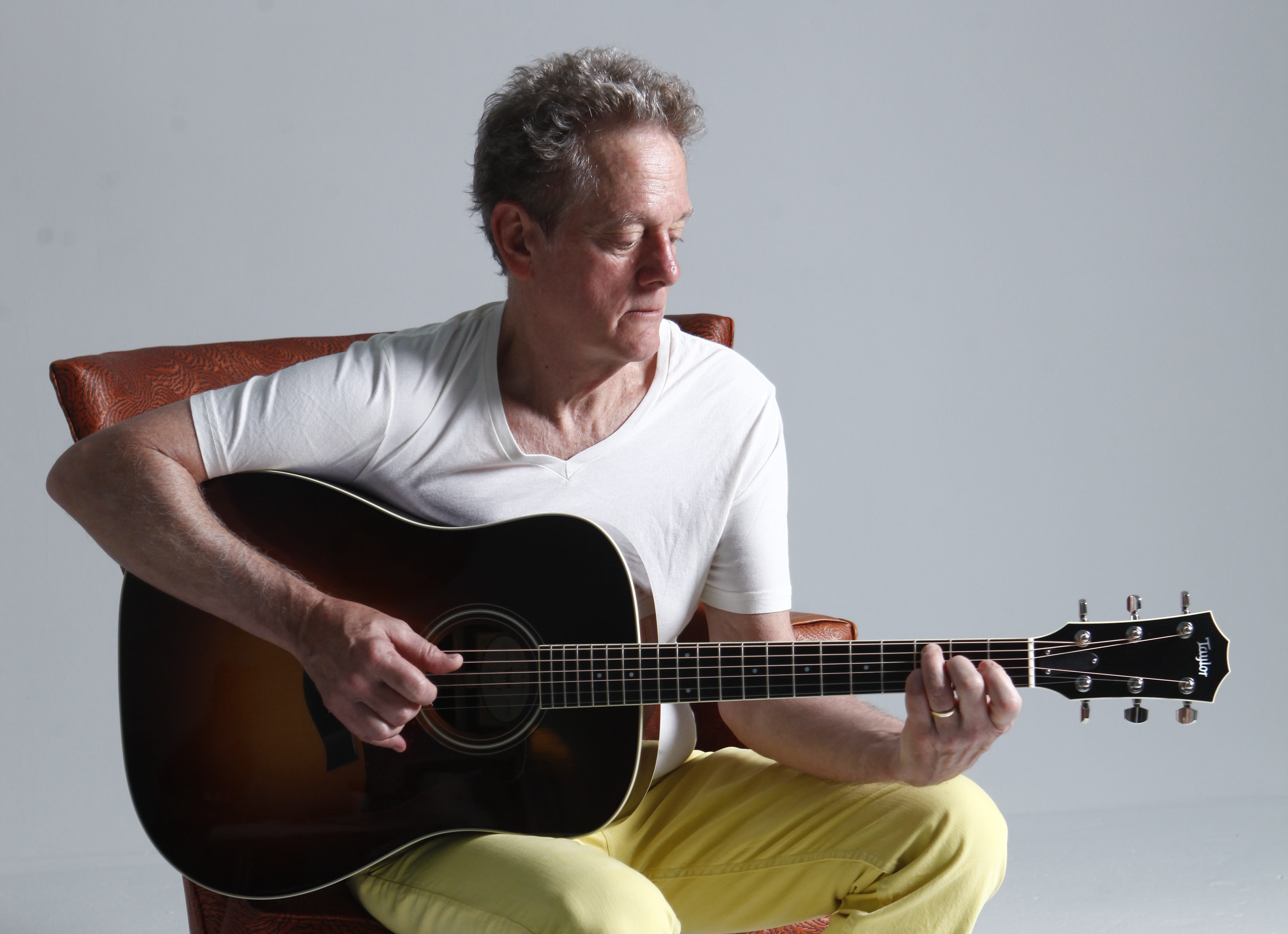 Photo of Professor Michael Bacon seated playing an acoustic guitar